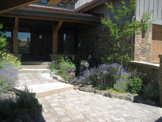 Entry planted with hardy perennials and pavers. Enhanced native tumbled pavers with stone slab steps.